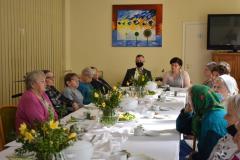 Zdjęcie przedstawia 12 mieszkanek siedzących przy stole wraz z główną księgową i zastępcą dyrektora którzy wspominają śp. Ewę Kwiecińską pomysłodawcę projektu ZDROWY STYL ZYCIA