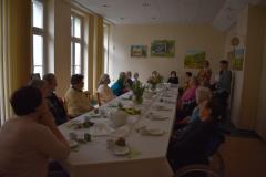 Zdjęcie przedstawia 15 mieszkańców siedzących przy stole wraz z główna księgową oraz trzy terapeutki przed rozpoczęciem zajęć