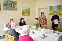 Zdjęcie przedstawia dwie terapeutki przygotowujące się do rozpoczęcia spotkania oraz sześciu mieszkańców siedzących przy stole