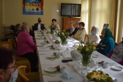 Zdjęcie przedstawia dziewięć mieszkanek siedzących przy stole wraz z zastępcą dyrektora oraz główną księgową