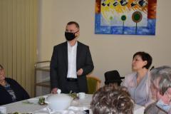 Zdjęcie przedstawia zastępcę dyrektora który składa uczestnikom spotkania życzenia wielkanocne, przy stole siedzi główna księgowa oraz cztery mieszkanki