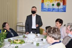 Zdjęcie przedstawia zastępcę dyrektora który wita uczestników spotkania, przy stole siedzi główna księgowa oraz cztery mieszkanki