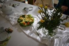 Zdjęcie przedstawia elementy dekoracji, przystrojony stół, wazon z bukszpanem żonkilami i gałązkami wierzby oraz półmisek z nadziewanymi jajami