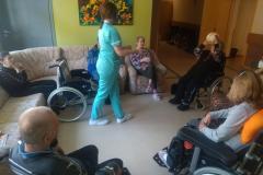 Fizjoterapeuta podczas grupowych zajęć usprawniających na segm. E1 rzut piłką do mieszkanki siedzącej na wózku