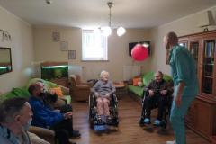 Mieszkańcy na wózkach inwalidzkich z segm. A2 podczas grupowych usprawniających z fizjoterapeuta odbijanie balonika
