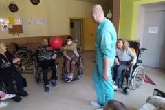 Mieszkańcy na wózkach inwalidzkich z segm. E1 podczas grupowych usprawniających z fizjoterapeuta odbijanie balonika
