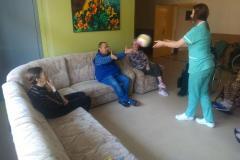Fizjoterapeuta podczas grupowych usprawniających na segm. E1 rzut piłką do mieszkanki siedzącej na wózku