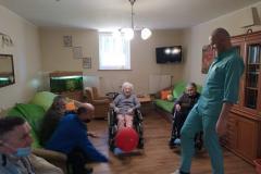 Mieszkańcy na wózkach inwalidzkich z segm. A2 podczas grupowych zajęć usprawniających z fizjoterapeuta odbijanie -balonika