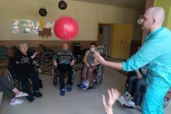 Mieszkańcy na wózkach inwalidzkich z segm. E1 podczas grupowych zajęć usprawniających z fizjoterapeuta odbijanie -balonika