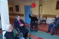 Mieszkańcy na wózkach inwalidzkich z segm. E2 podczas grupowych zajęć usprawniających z fizjoterapeuta odbijanie -balonika