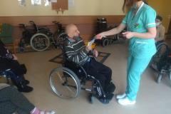 Fizjoterapeuta wręcza nagrodę mieszkańcowi segm. E1 najbardziej aktywnemu podczas zajęć usprawniających