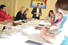 Zdjęcie przedstawia zastępcę dyrektora, który przedstawia siedzącemu przy stole Zespołowi Kontroli Zarządczej Plan zebrania